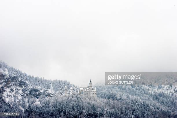 TOPSHOT Snowcovered forests surround the Neuschwanstein Castle in Hohenschwangau on February 22 2018 PHOTO / dpa / Jonas Güttler / Germany OUT