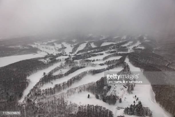 Snow-covered golf course in Tomakomai city in Hokkaido in Japan daytime aerial view from airplane