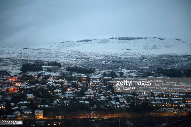 Snow-covered homes are illuminated at dusk in the village of Marsden, near Manchester in northern England on December 4, 2020.