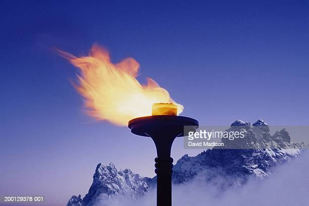 Snow-covered mountains behind flaming torch (Digital Composite)