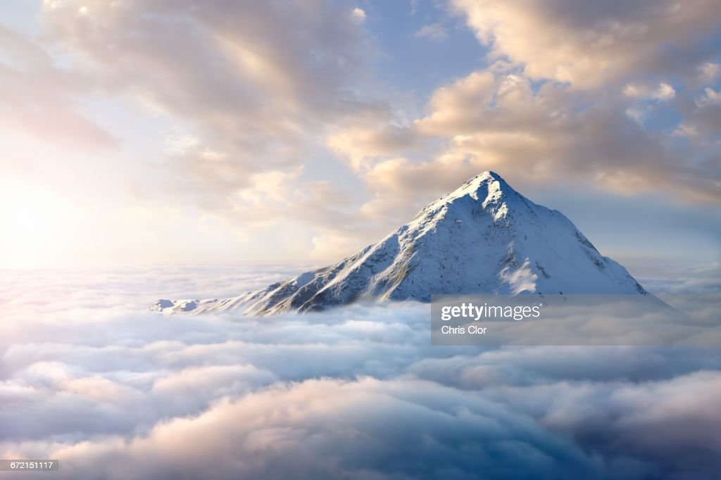 Snow-covered mountaintop above clouds : ストックフォト