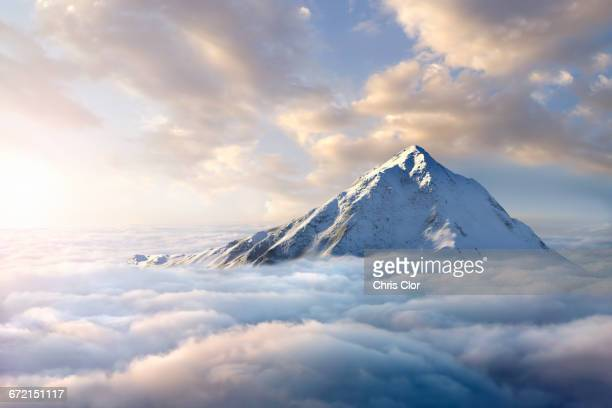 snow-covered mountaintop above clouds - bergpiek stockfoto's en -beelden