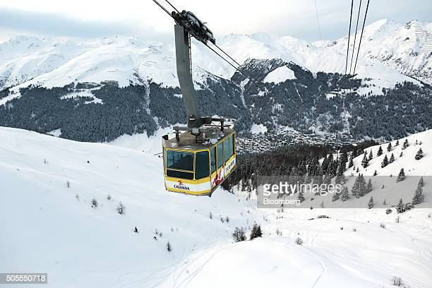 Snowcovered residential and commercial buildings stand below as the Jakobshorn cable car travels up the mountain above the town of Davos Switzerland...