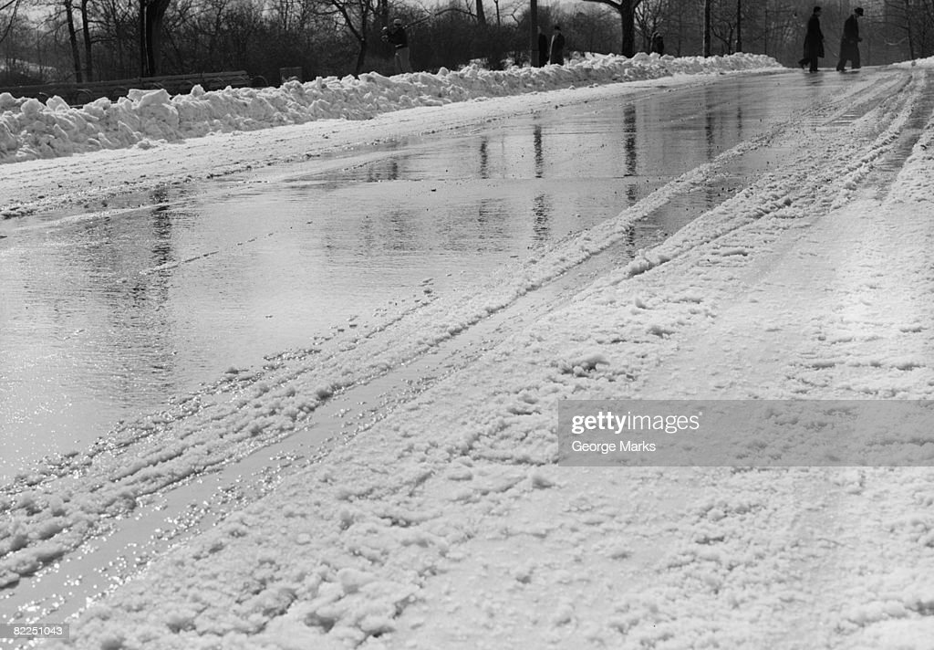 Snow-covered road in winter, with people in background : Stock Photo