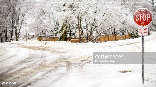Snow-covered road intersection and stop sign in winter