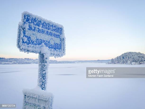 A Snow-Covered Roadside Sign in Rural Buskerud, Norway Wintertime