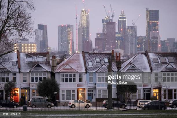Snow-covered roofs and the glowing lights in the porches of south London Edwardian homes and residential high-rise towers under construction, on 8th...