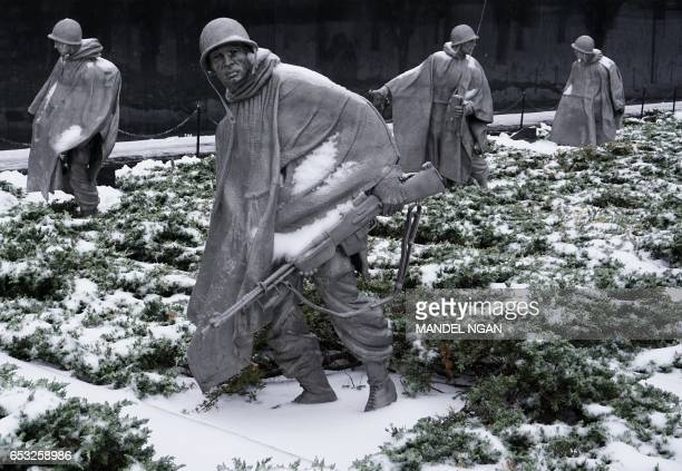 Snowcovered statues in the Korean War Veterans Memorial are seen on March 14 2017 in Washington DC Winter Storm Stella dumped snow and sleet Tuesday...