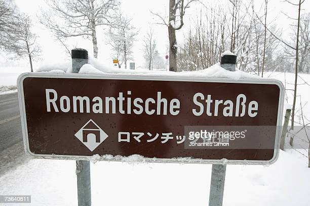 A snowcovered street sign of 'Romantische Strasse' at Neuschwanstein Castle on March 20 near Fussen Germany As temperatures dropped down snow...