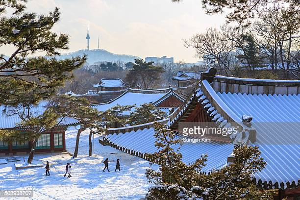 Snow-covered view of Changgyeonggung Palace with a distant city view at background, Seoul, Korea.