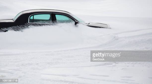 a snowdrift forms around a parked car - buried stock pictures, royalty-free photos & images