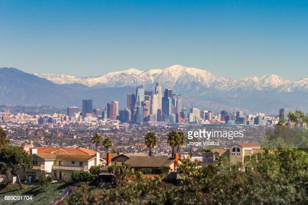 Snowed peaks mountains and downtown Los Angeles cityscape