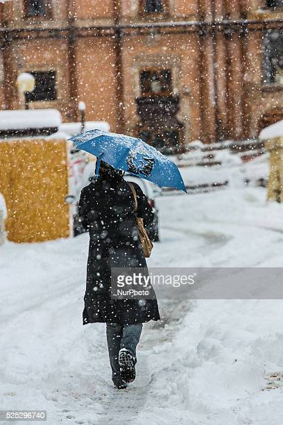 Snowfall in L'Aquila the regional capital of Abruzzo on November 26 2013 Some roads were blocked with severe transportation problem In photo woman...