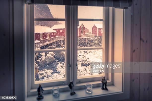 Snowfall seen through the window in Nusfjord village in the Flakstadøya Island in Lofoten Archipelago, in Nordland county in Norway.
