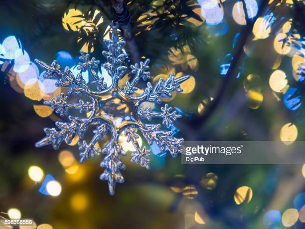 snowflake pattern christmas ornament hanging in the tree - winter solstice stock photos and pictures
