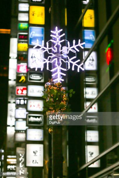 Snowflake shaped Christmas lights against sign boards and neon on Konbaru Dori Street in Ginza
