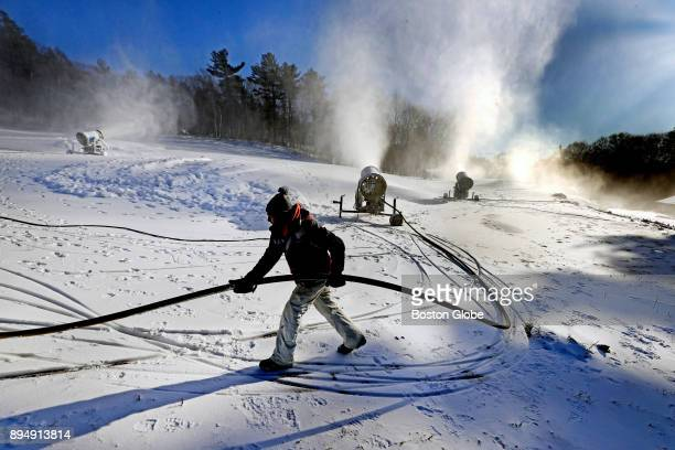 Snowmaker Lincoln Faria moves a water hose to prevent it from getting buried in the snow at the Blue Hills Ski Area in Canton MA where snowmaking on...