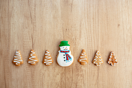 Snowman cookie surrounded by Christmas trees cookies on a wooden background, directly above view - gettyimageskorea