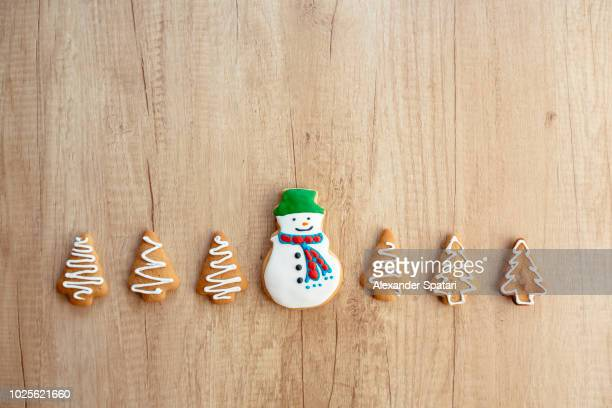 snowman cookie surrounded by christmas trees cookies on a wooden background, directly above view - christmas cookies stock pictures, royalty-free photos & images