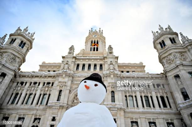 Snowman is built outside the Cibeles Palace in Madrid on January 10, 2021. - Snowstorms in Spain left three people dead and caused chaos across much...
