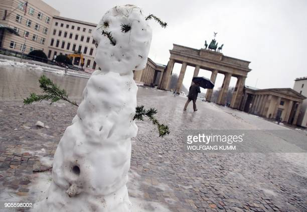 Snowman is pictured in front of the Brandenburg Gate in Berlin on January 16, 2018. / AFP PHOTO / dpa / Wolfgang Kumm / Germany OUT