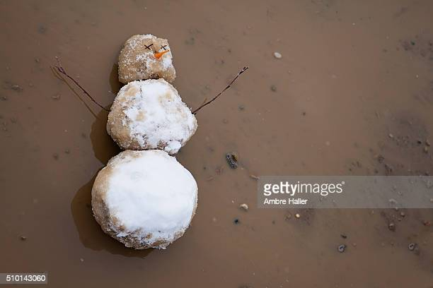 Snowman melting in a puddle