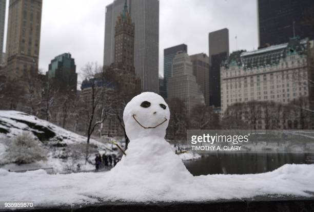A snowman on the Gapstow Bridge in Central Park in New York March 21 2018 as the fourth nor'easter in a month hits the tristate area on the first...