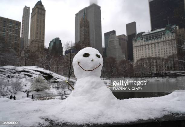 TOPSHOT A snowman on the Gapstow Bridge in Central Park in New York March 21 2018 as the fourth nor'easter in a month hits the tristate area on the...