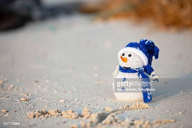 Snowman ornament sitting on beach in the Caribbean