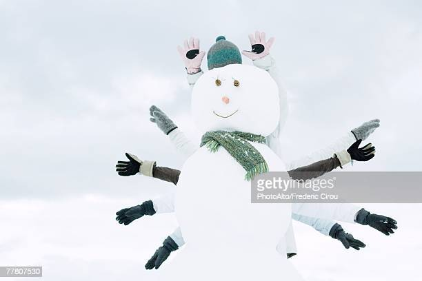 snowman, several people's arms emerging from behind - funny snow stock photos and pictures