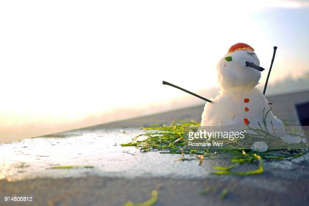 Snowman sitting on wall in the sun, melting