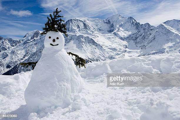 a snowman with mountains behind - bonhomme de neige photos et images de collection