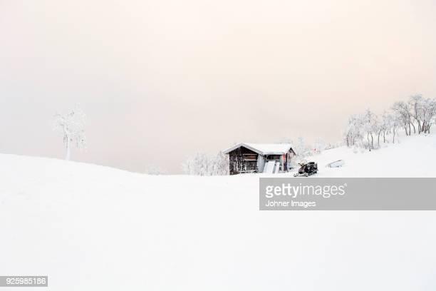 snowmobile and wooden shed in snow field - schneebedeckt stock-fotos und bilder