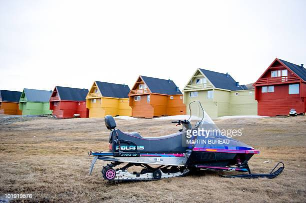 A snowmobile is parked in front of colourful houses in Longyearbyen on June 8 2010 AFP PHOTO / MARTIN BUREAU