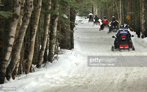 Snowmobilers ride along ITS 84 in Oquossoc on Saturday January 12 2013