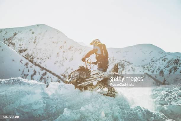 moto de neve através de uma deriva de neve. - snowmobiling - fotografias e filmes do acervo