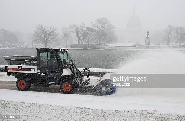 A snowplow blows snow from the steps of the Capitol Reflecting Pool at the US Capitol in Washington DC January 21 as snow falls during a storm The...