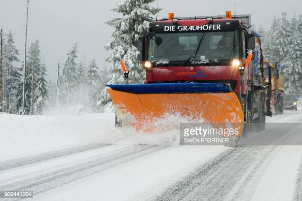 A snowplow cleans a road from snow near Torfhaus northern Germany on January 18 2018 Weather forecasts predict a heavy storm and snow over Germany /...