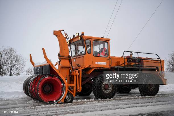 A snowplow clears a road leading to the French Alps ski resort of Les Menuires on January 4 2018 after the region was swept by storm Eleanor Winter...