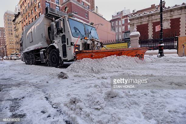 A snowplow clears snow on East 91st Street on the east side of Manhattan January 22 2014 in New York The northeastern US shivered amid heavy snowfall...