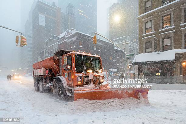 TOPSHOT A snowplow clears snow on Lexington Avenue during the snowstorm January 2016 in New York A deadly blizzard with bonechilling winds and...