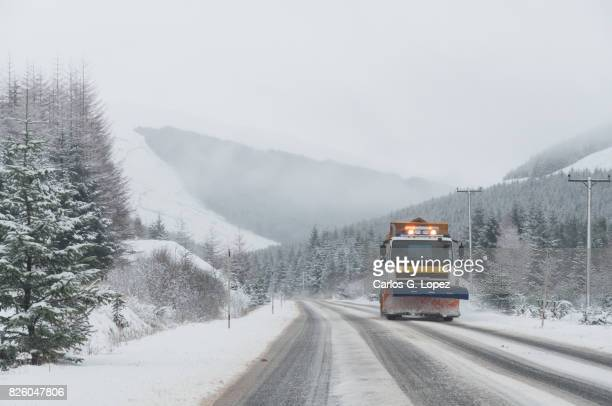 Snowplow clears the snow off a road near forest and mountains