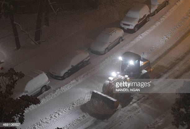 A snowplow is in action overnight to clear a residential street in Chevy Chase Maryland as the snows continues to fall on February 13 2014 A deadly...