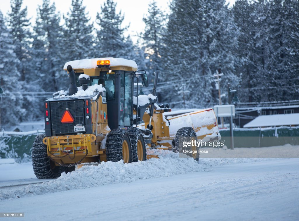 A snowplow tractor removes snow from Highway 50 on January