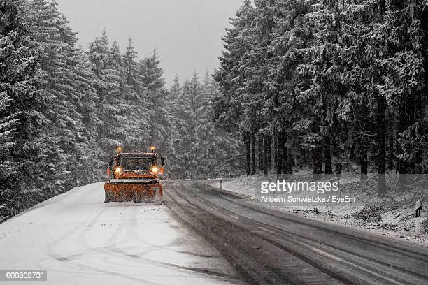 Snowplow Vehicle On Country Road Amidst Trees