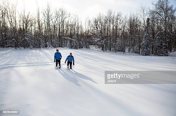 Snowshoeing Couple in The Midwest on a Sunny Winter Day.