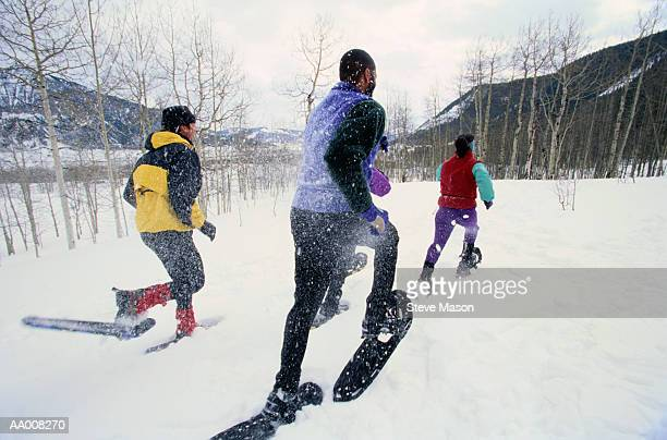 snowshoers racing across a snow covered field - winter sport stock pictures, royalty-free photos & images