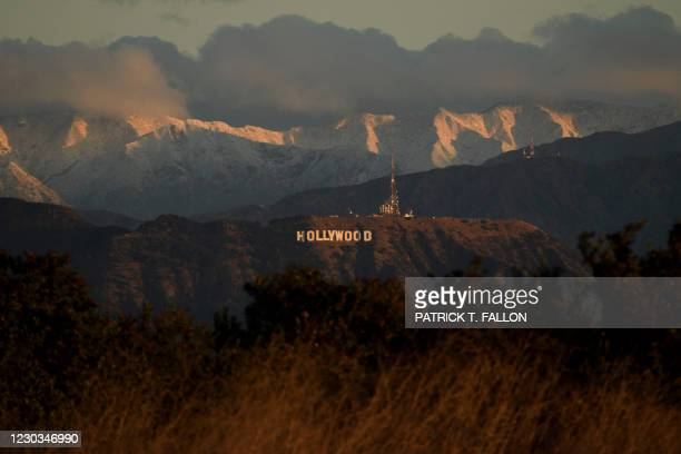 Snow-topped mountains stand behind the Hollywood sign after sunrise following heavy rains as seen from the Kenneth Hahn State Recreation Area on...