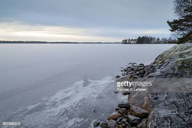 snowy cliff at a shore and frozen and snowy lake in finland at dawn in the winter. - seeufer stock-fotos und bilder