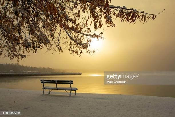 snowy golden sunrise with bench looking over lake - スカネアトレス湖 ストックフォトと画像